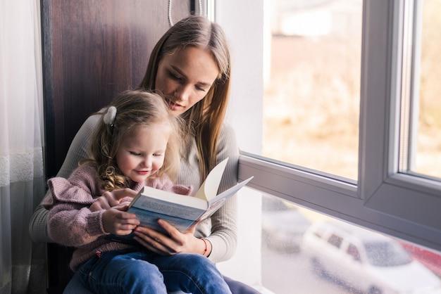 Mãe feliz e filha lendo livro, sentado no sofá confortável na sala de estar