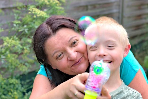 Mãe feliz e filho com a síndrome de down que joga em um jardim.