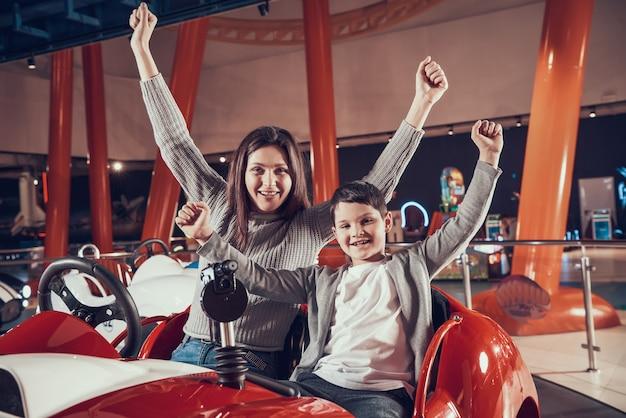 Mãe feliz e filho de sorriso que sentam-se no carro do brinquedo.
