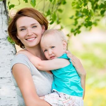 Mãe feliz e filho pequeno no campo - retrato ao ar livre