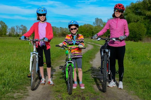 Mãe feliz e filhos em bicicletas, andar de bicicleta ao ar livre, esporte ativo da família