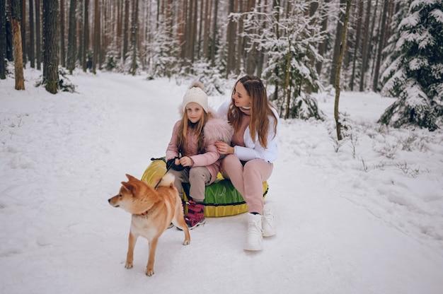 Mãe feliz e garotinha linda em trajes quentes rosa caminhando se divertindo em um tubo inflável de neve