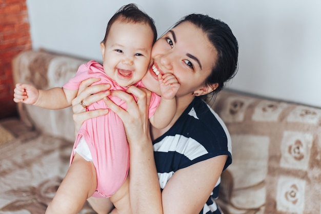 Mãe feliz e menina em roupas cor de rosa, jogando em casa