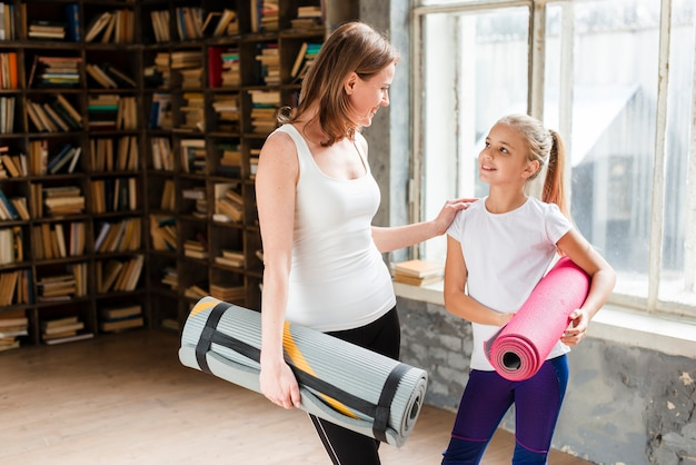 Mãe feliz e menina segurando tapetes de ioga