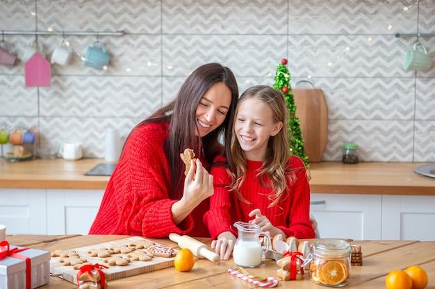 Mãe feliz e meninas cozinhando biscoitos de natal na cozinha