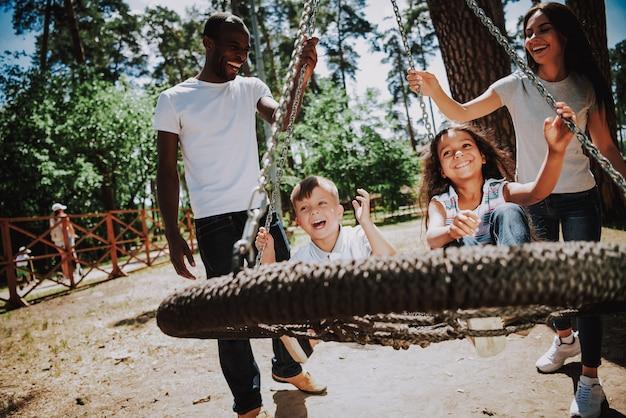 Mãe feliz e pai empurrando swing joyful kids