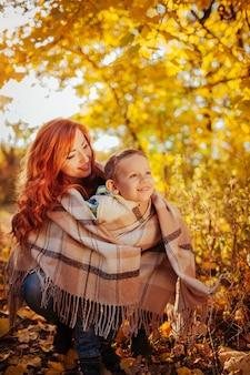 Mãe feliz e seu filho pequeno abraçando e se divertindo na floresta de outono