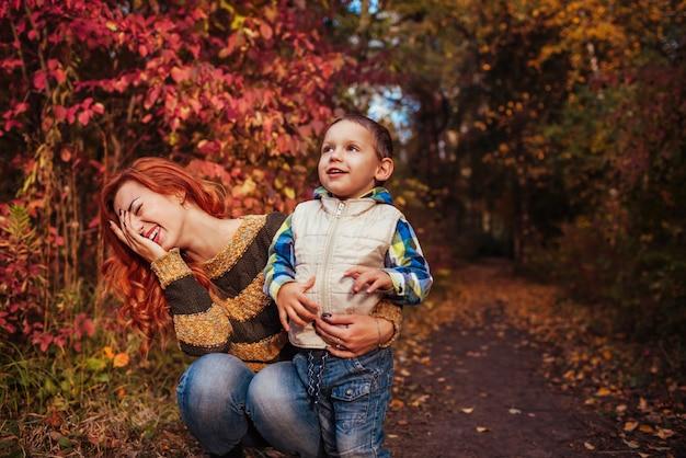 Mãe feliz e seu filho se divertindo na floresta de outono criança e mãe estão rindo