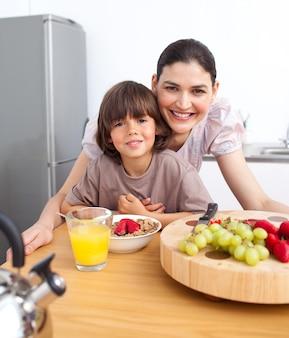 Mãe feliz e seu filho tomando café da manhã