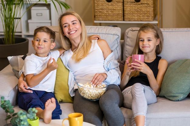 Mãe feliz e seus filhos comendo pipoca