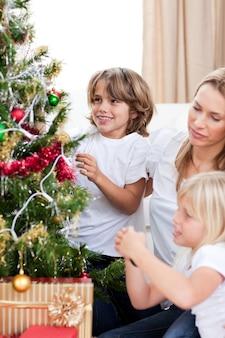 Mãe feliz e seus filhos pendurados em decorações de natal