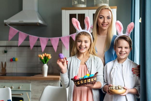 Mãe feliz e seus sorridentes, adoráveis filhos segurando ovos coloridos e genuinamente feliz páscoa