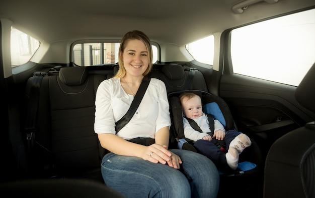 Mãe feliz e sorridente com seu bebê no banco de trás