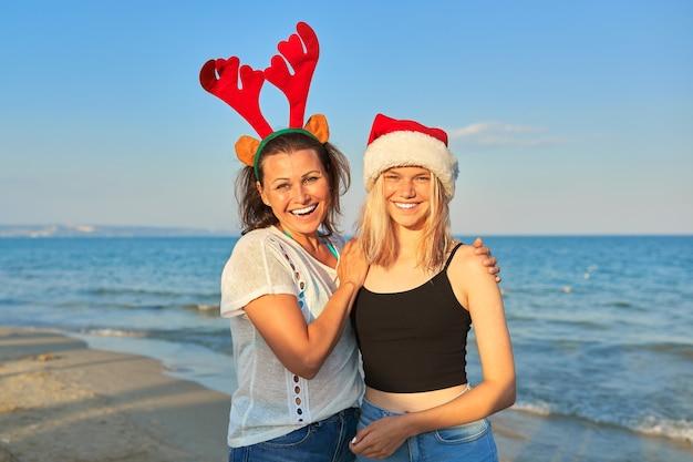 Mãe feliz e sorridente e filha adolescente com chapéu de papai noel na praia