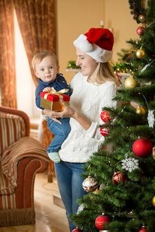 Mãe feliz e sorridente e filho na árvore de natal