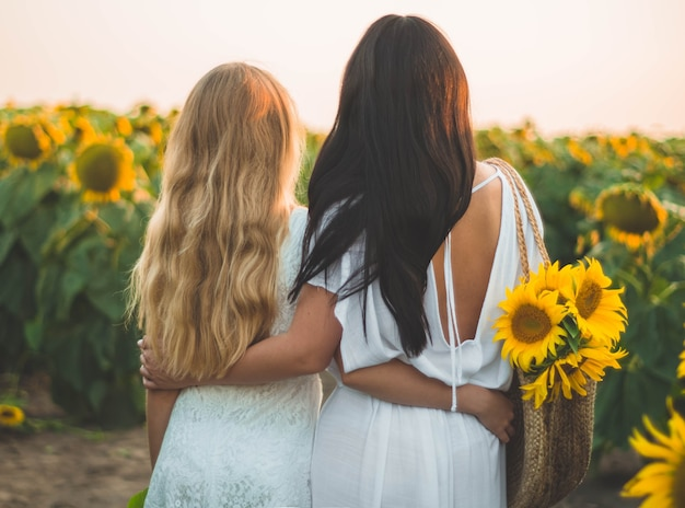 Mãe feliz e sua filha adolescente no campo de girassol. felicidade do estilo de vida ao ar livre