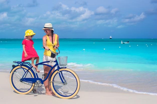 Mãe feliz e sua filha andando de bicicleta em uma praia tropical