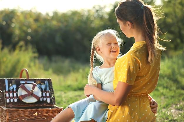 Mãe feliz e sua filha no piquenique no parque