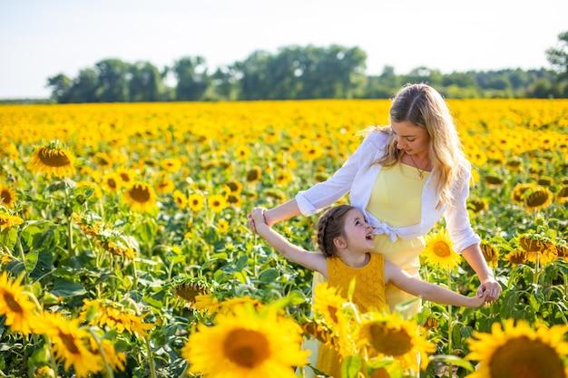 Mãe feliz e sua filha pequena no campo de girassóis