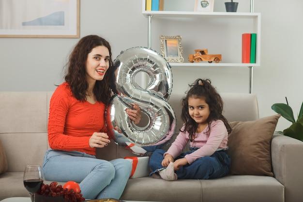 Mãe feliz e sua filha pequena sentada em um sofá com um balão em forma de número oito sorrindo alegremente, se divertindo juntos na sala de estar iluminada, comemorando o dia internacional da mulher, 8 de março