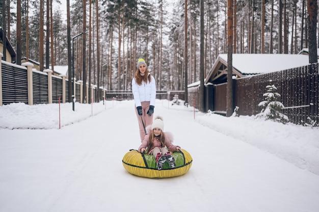Mãe feliz e uma garotinha linda em roupas quentes rosa andando se divertindo, passeios em tubo de neve inflável na floresta de inverno frio branco nevado ao ar livre