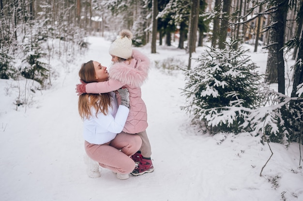 Mãe feliz e uma linda garotinha com outwear quente rosa caminhando se divertindo e se abraçando na floresta de coníferas de inverno branco nevado com bosques de abetos ao ar livre