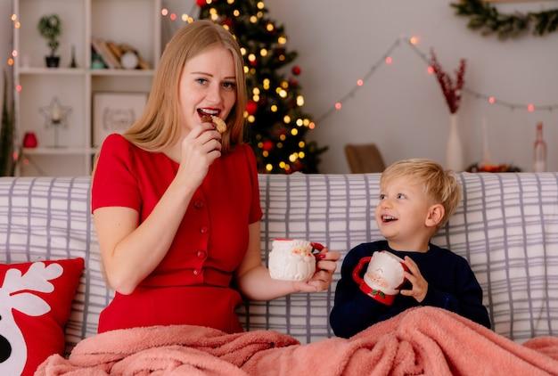 Mãe feliz em um vestido vermelho com seu filho pequeno sentado em um sofá, debaixo do cobertor, bebendo chá em canecas, comendo biscoitos, sorrindo em um quarto decorado com árvore de natal na parede