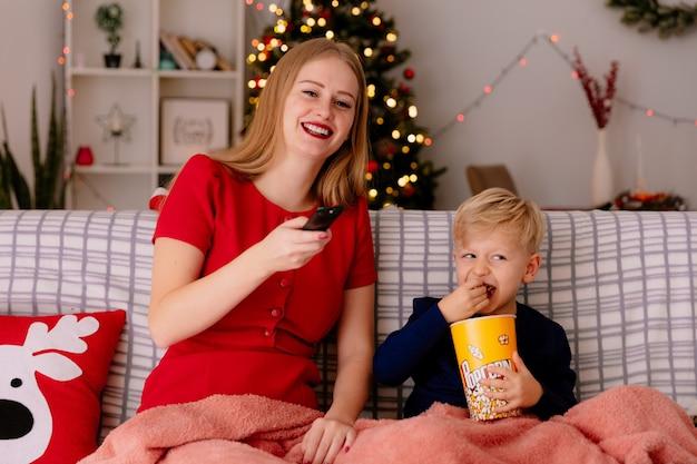 Mãe feliz em um vestido vermelho com seu filho pequeno sentado em um sofá sob o cobertor com um balde de pipoca assistindo tv juntos em um quarto decorado com árvore de natal na parede