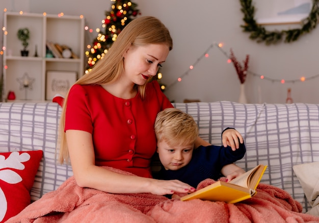 Mãe feliz em um vestido vermelho com seu filho pequeno sob o cobertor lendo um livro em um quarto decorado com uma árvore de natal na parede