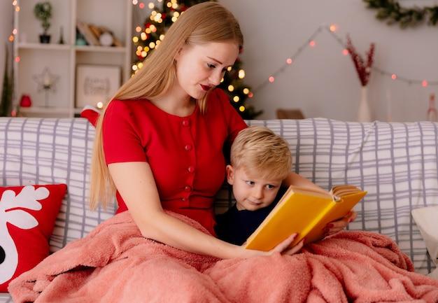 Mãe feliz em um vestido vermelho com seu filho pequeno sob o cobertor lendo um livro em uma sala decorada com uma árvore de natal ao fundo