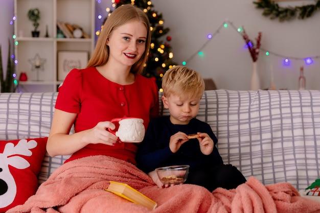 Mãe feliz em um vestido vermelho com uma xícara de chá e seu filho comendo biscoitos debaixo do cobertor em um quarto decorado com uma árvore de natal ao fundo