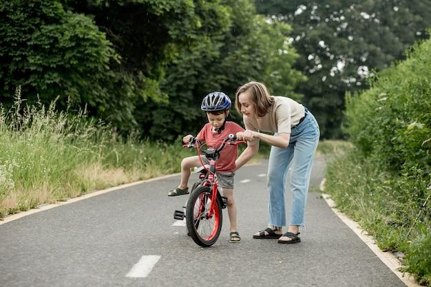 Mãe feliz ensina filho filho a andar de bicicleta na ciclovia