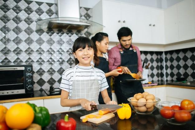 Mãe feliz ensinar a filha a cortar legumes preparando ingredientes