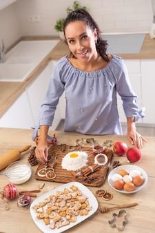 Mãe feliz fazendo bolos de natal e gringerbreads. ela usa ovos, farinha, canela e laranjas secas como decoração.