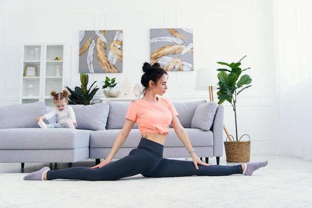 Mãe feliz fazendo exercícios de manhã em pose de ioga enquanto sua filha brincando em casa. jovem mãe adorável se divertindo praticando meditação relaxante no fim de semana livre de estresse com o bebê.