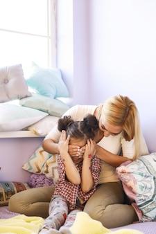 Mãe feliz fechou os olhos da filha sentada no sofá com muitas almofadas perto da janela
