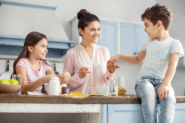 Mãe feliz. jovem mãe morena, alerta e atraente, sorrindo e dando pílulas para seu filho sentado na mesa e sua filha tomando café da manhã