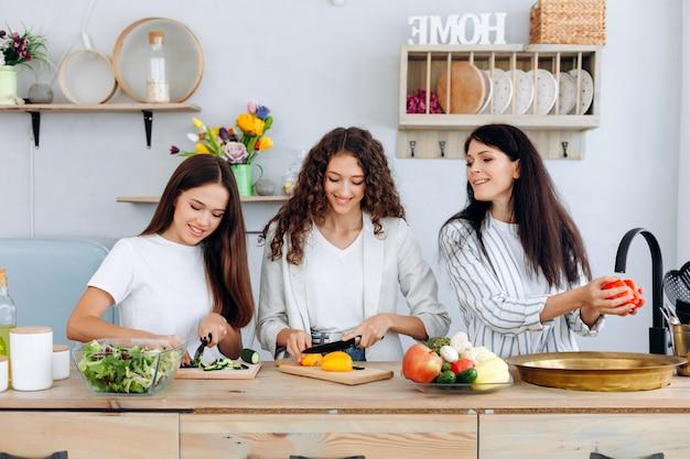 Mãe feliz lavando legumes e suas filhas juntos em uma cozinha estão preparando uma salada