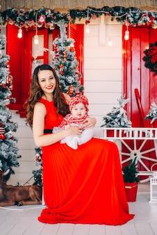 Mãe feliz no vestido vermelho com sua filha pequena no vestido na sala de férias decoradas com uma árvore de natal e uma coroa de flores