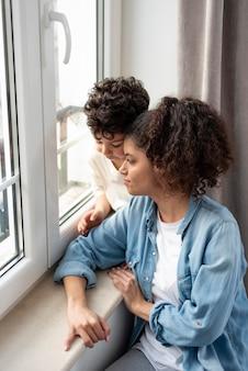 Mãe feliz olhando pela janela com o filho