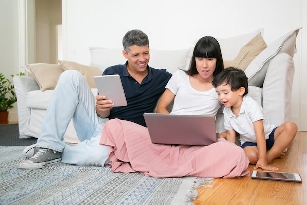 Mãe feliz, pai e garotinho bonito usando computadores, sentado no chão do apartamento, aproveitando o tempo de lazer juntos.