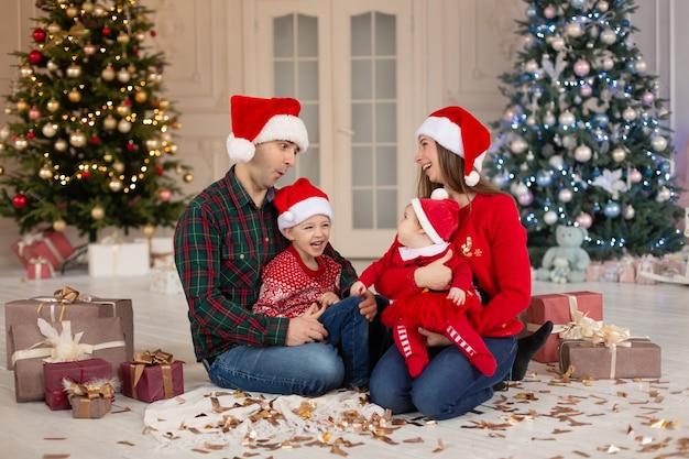 Mãe feliz, pai, filha e filho com chapéu de papai noel