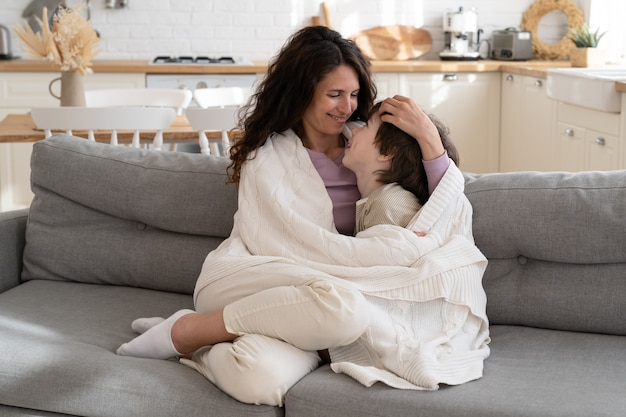 Mãe feliz passando um tempo com a criança em casa no fim de semana abrace o menino rindo debaixo do cobertor e sente-se no sofá