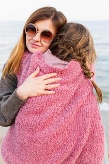 Mãe feliz que abraça a rapariga