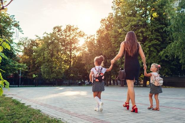 Mãe feliz que encontra suas filhas dos miúdos após a escola primária das classes ao ar livre.