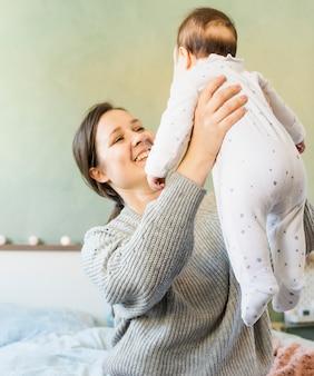 Mãe feliz que joga com bebê