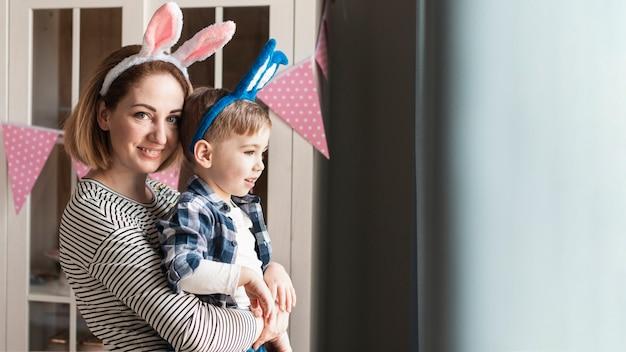 Mãe feliz, segurando a criança com orelhas de coelho