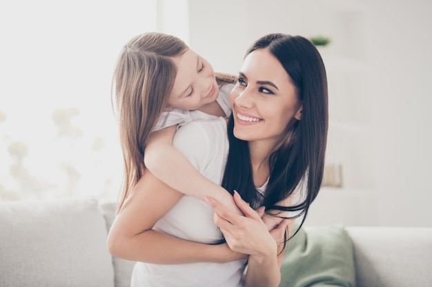 Mãe feliz segurando a filhinha nas costas na casa da sala de estar dentro de casa