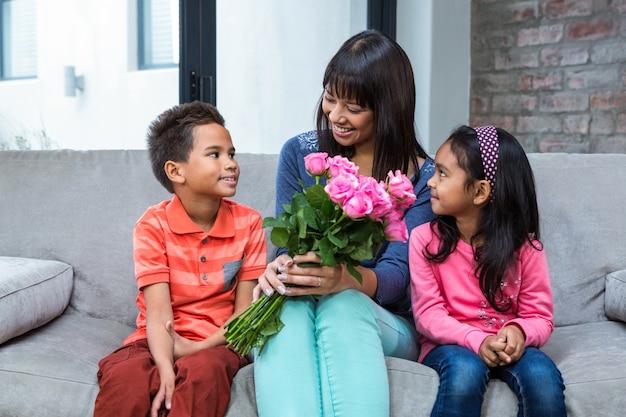Mãe feliz segurando rosas sentadas com seu filho e filha no sofá