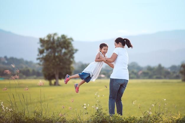 Mãe feliz segurando seu filho e girando com diversão no campo no tom de cor vintage
